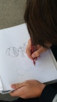 Eighth grader Matthew sketching a cartoon body LAUREN LEE, STAFF PHOTOGRAPHER 	LAUREN LEE, STAFF PHOTOGRAPHER